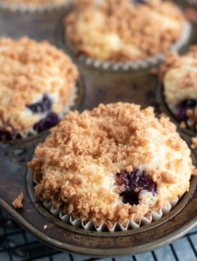 blueberry crumb muffins in a muffin pan