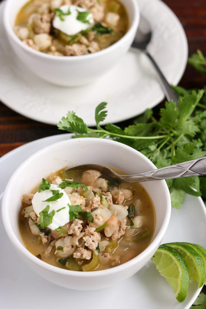 Two white bowls filled with white chicken chili sitting on white plates with cilantro on wood table.