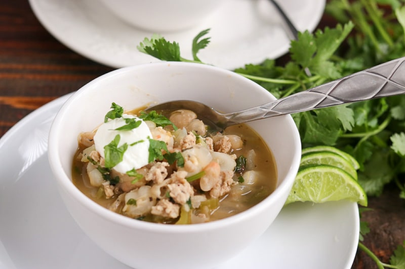 White chicken chili in white bowl on white plate with three lime wedges and cilantro on wood table.