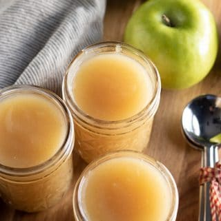 homemade applesauce in jars with granny smith apples and a towel