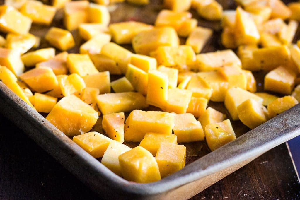 Closeup of cubed squash on baking sheet ready to be roasted.