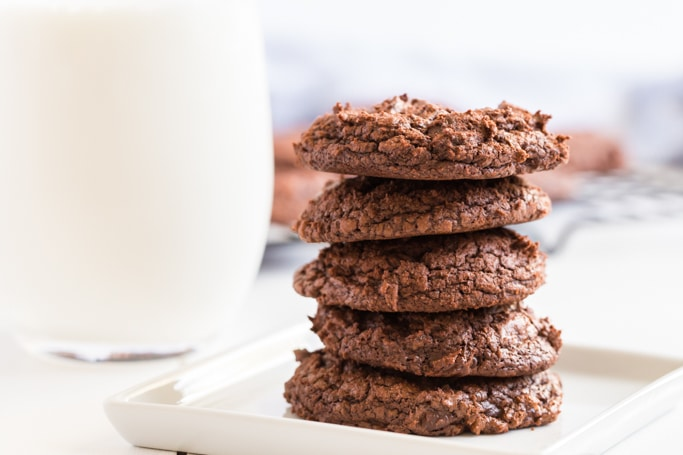stacked chocolate cookies with a glass of milk