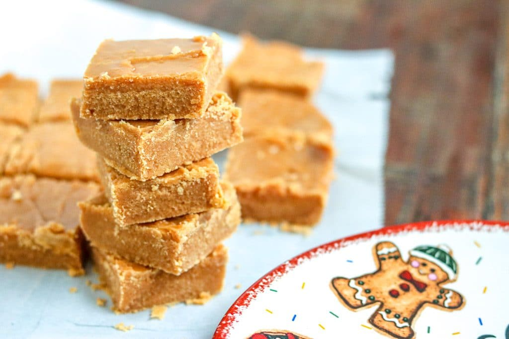 Caramel fudge squares stacked with more squares in the background on parchment paper.