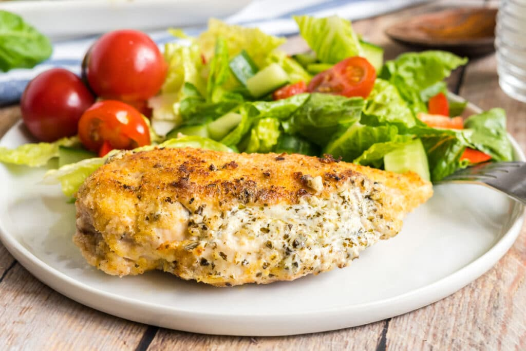 stuffed chicken on a white plate with a salad
