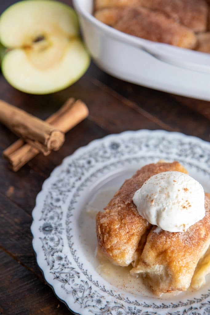 apple dumplings on a white plate with a scoop of icecream