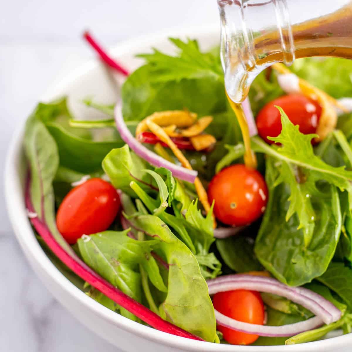 mustard vinaigrette being poured onto salad greens