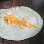 Adding cheese to flour tortilla on wooden table.