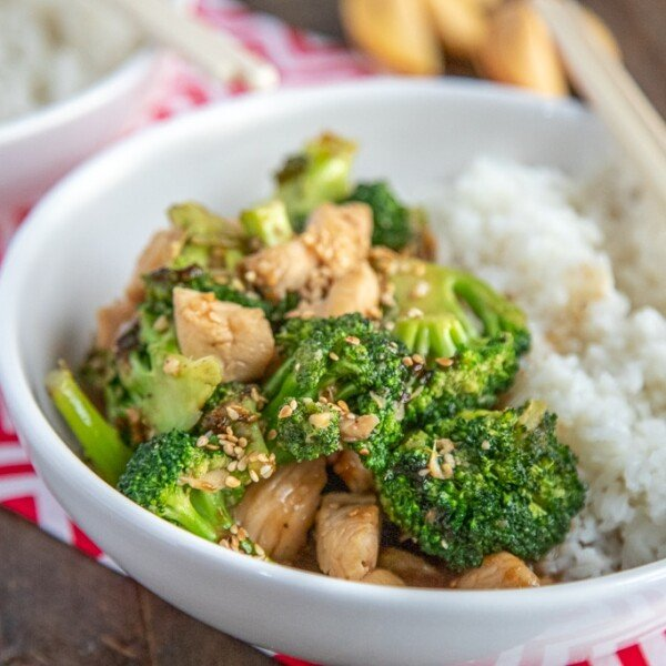 chicken broccoli stir fry in a white bowl with rice and chopsticks