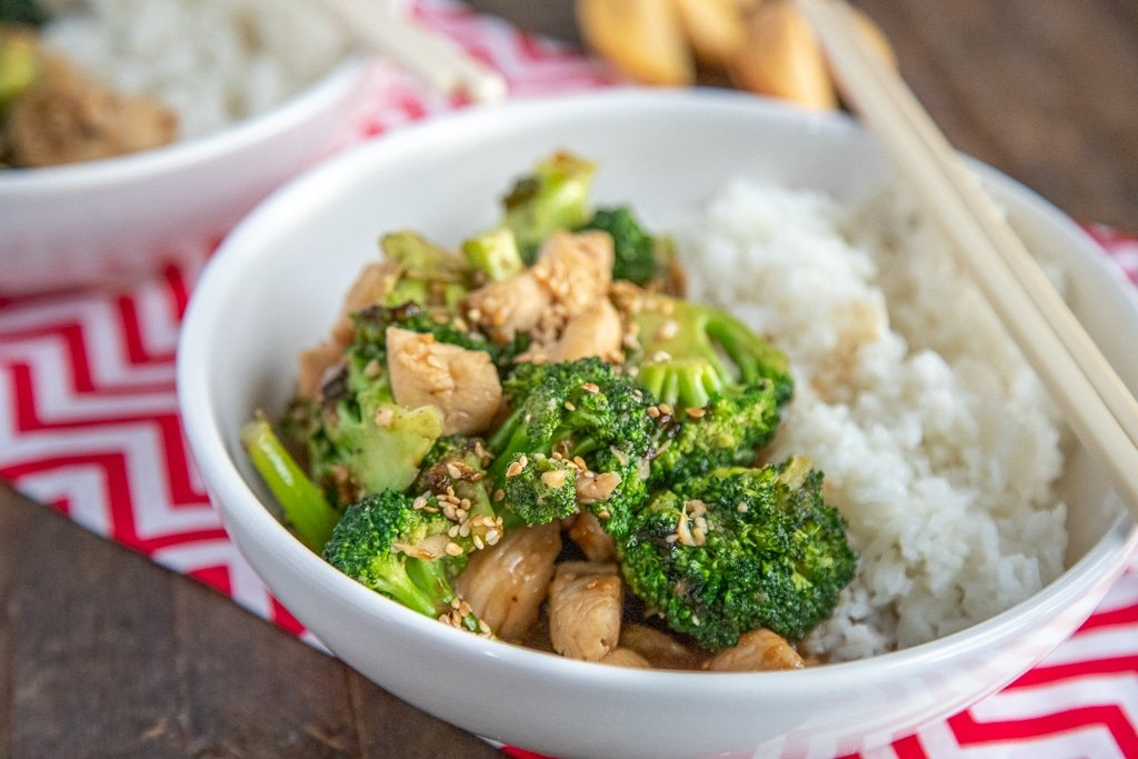 chicken broccoli stir fry in white bowl with rice, red and white napkin