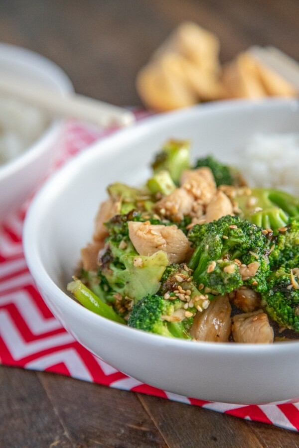 chicken and broccoli stirfry in a white bowl with a red and white chevron napkin