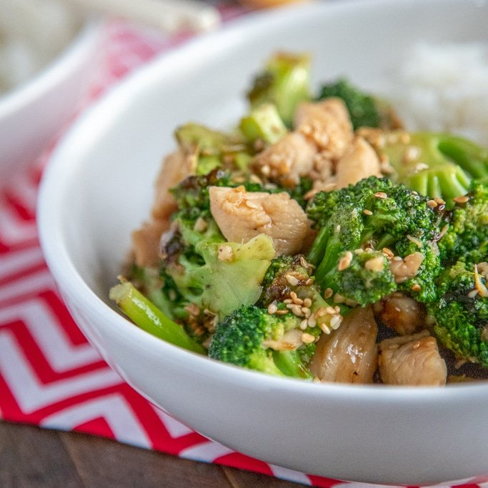 square pic of chicken broccoli stir fry in a white bowl with rice and chopsticks