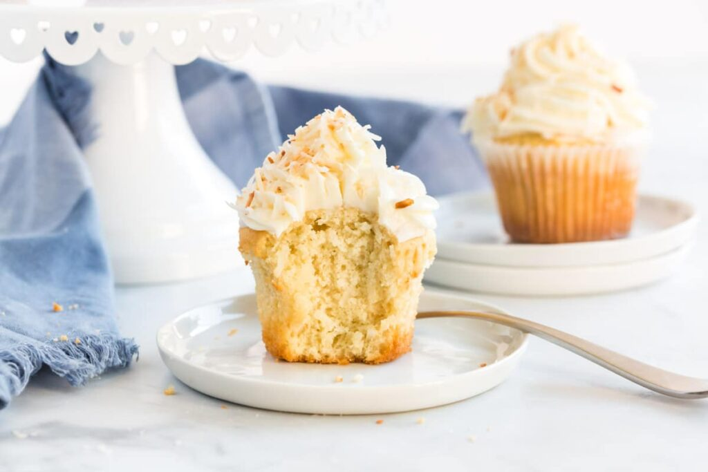 coconut cupcake on a white plate, cut open to show texture