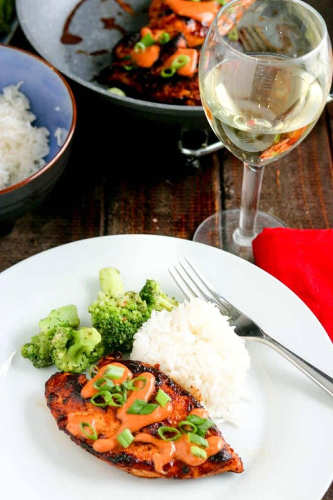 chicken diablo on a white plate, wine glass with rice and broccoli