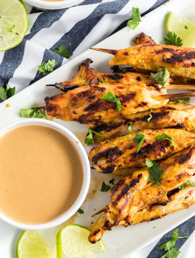 grilled chicken satay on a white platter with peanut sauce and a wedge of lime