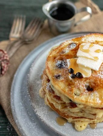 blueberry pancakes on a grey plate with silverware wrapped in red gingham ribbon