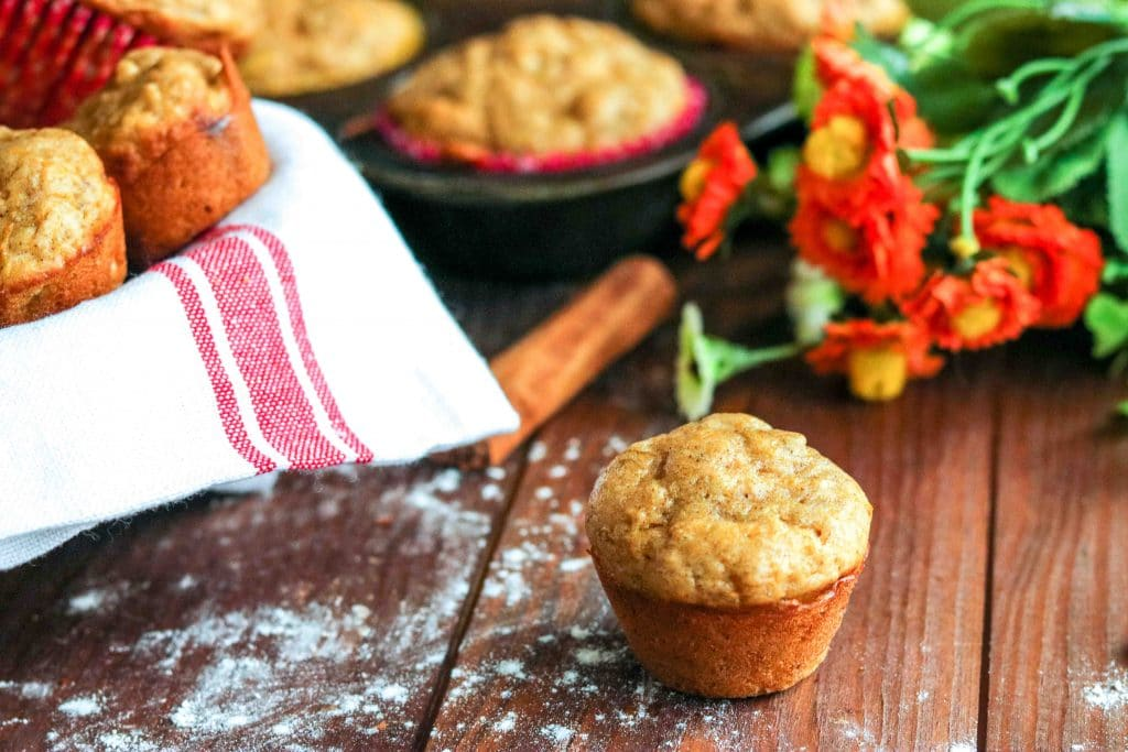 Butternut squash muffin on wooden table with more muffins in a muffin tin in background.