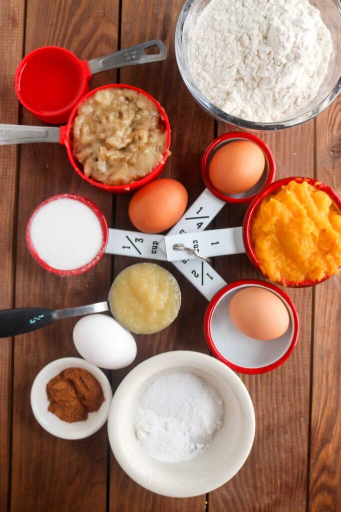 Overhead shot of butternut squash muffin ingredients in separate bowls on wooden table.