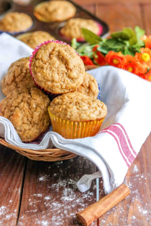butternut squash banana muffins in a basket lined with a kitchen towel