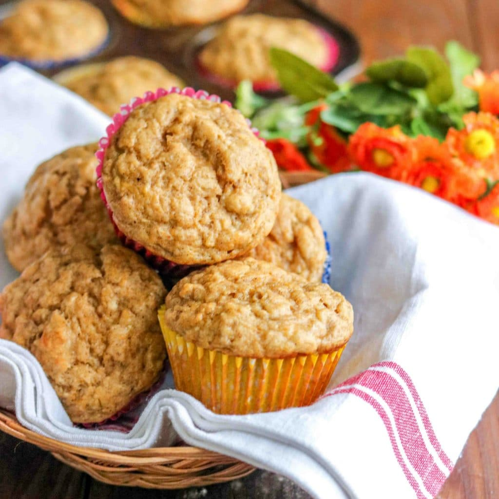 Butternut squash muffins in towel-lined basket with muffin tin filled with muffins in background.