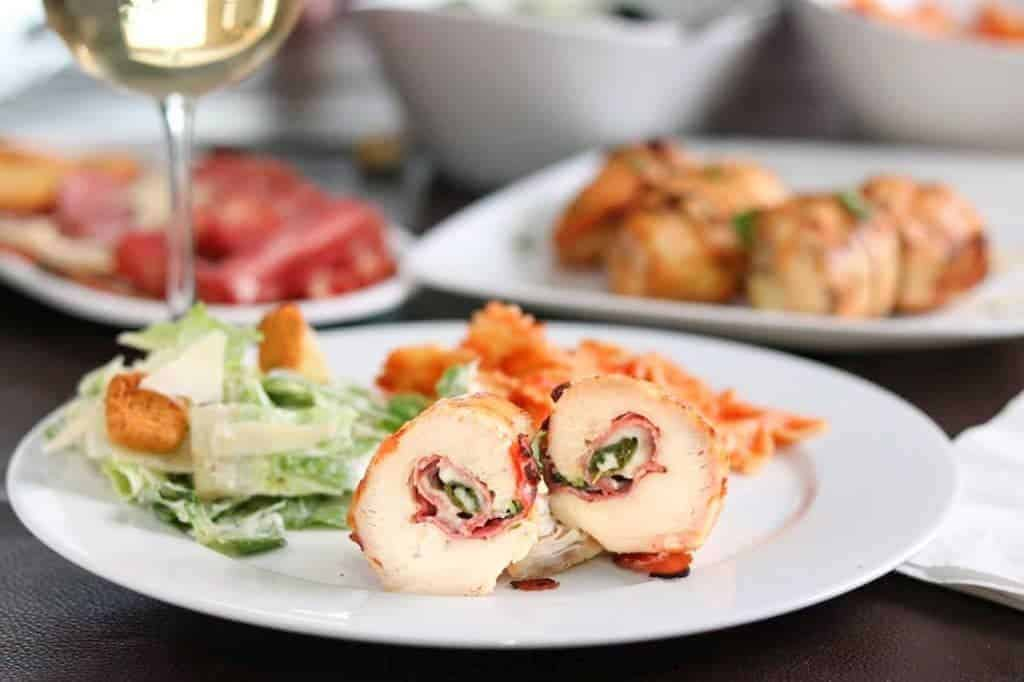These yummy chicken rollettes are seasoned with garlic, packed with prosciutto, creamy provolone and fresh basil, grilled to perfection and served with white wine, pasta, red sauce and a garlicky Caesar salad. Hello, summer!