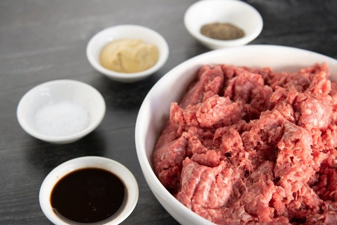beef burger ingredients with 4 little bowls