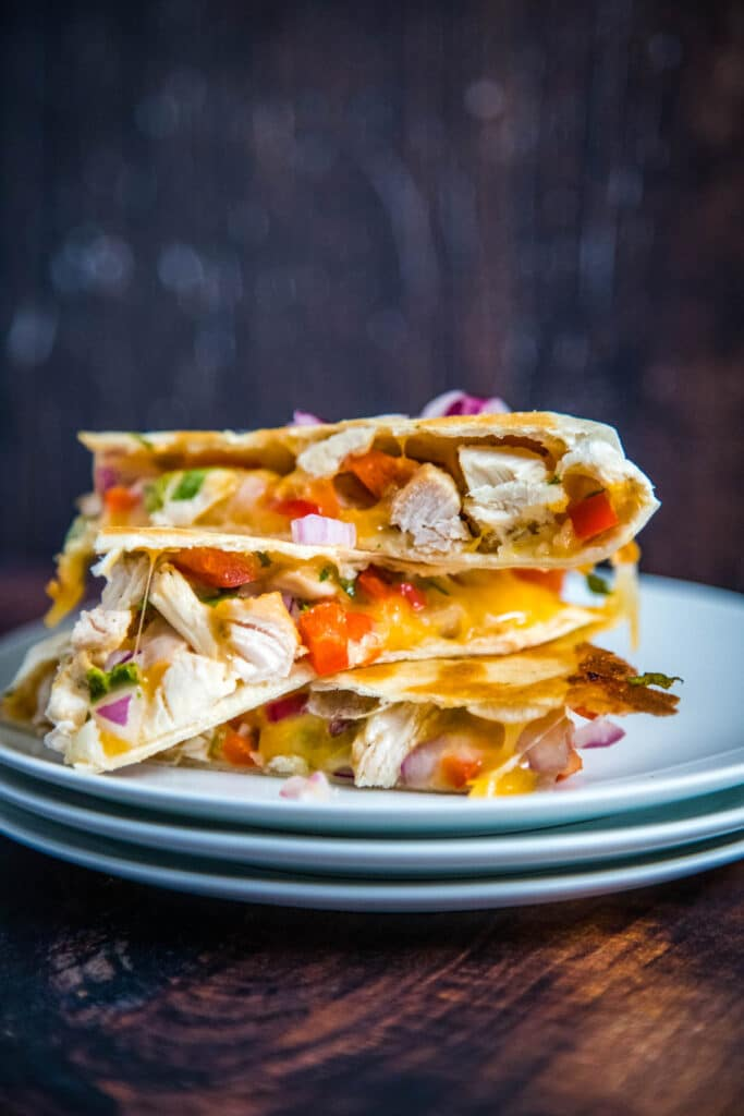 chicken quesadillas on a stack of white plates