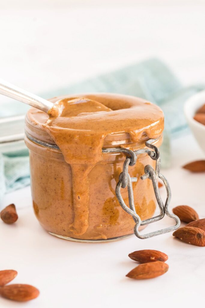 homemade almond butter in a jar, with a spoon. Almonds scattered around and a pale blue napkin in the background