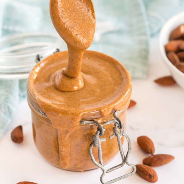 homemade almond butter in a jar, with a spoon drizzling it out. Almonds scattered around and a pale blue napkin in the background
