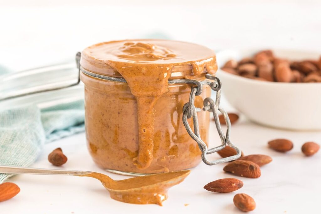homemade almond butter in a jar, with a spoon drizzling it out. Almonds scattered around