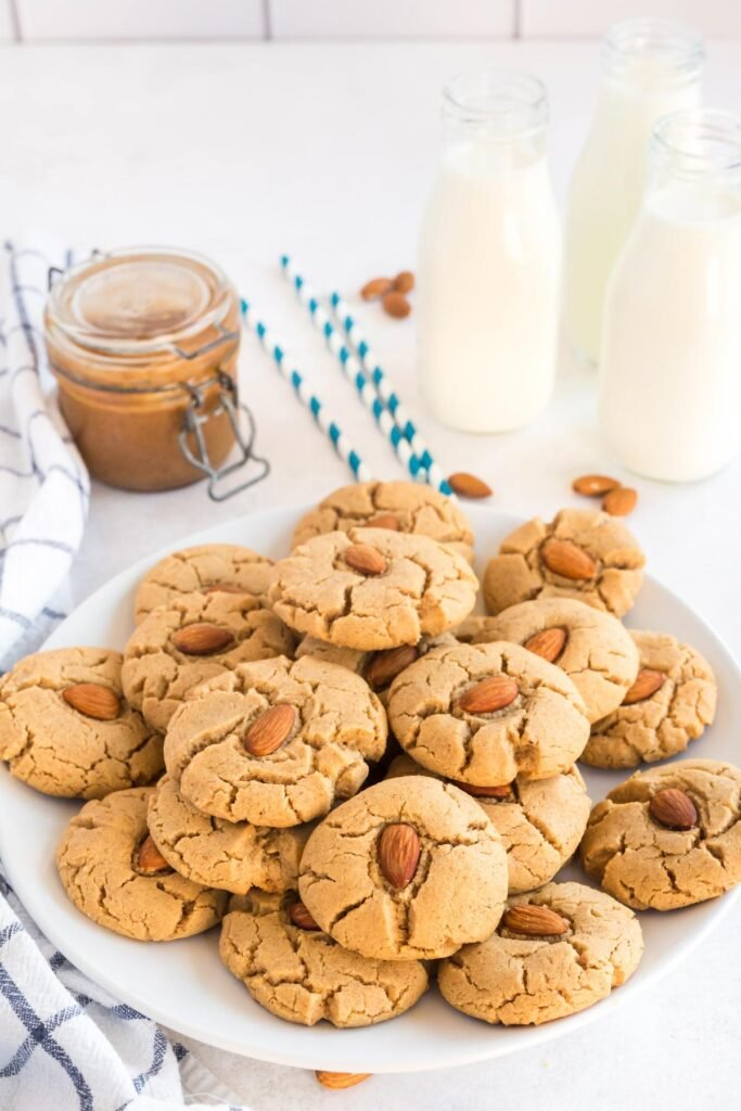almond butter cookies on a white plate with almonds, milk an d a jar of almond butter
