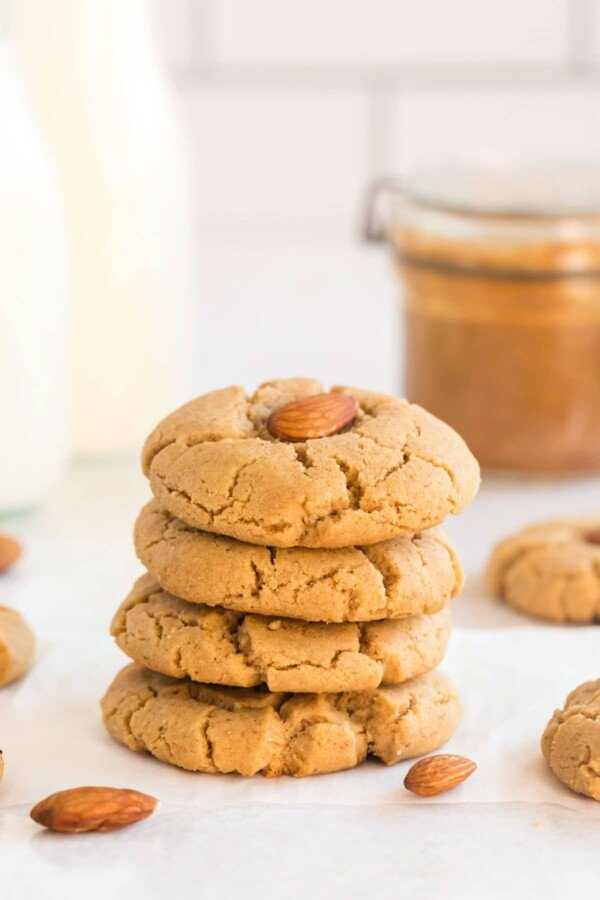 almond butter cookies stacked with almonds, milk and a jar of almond butter