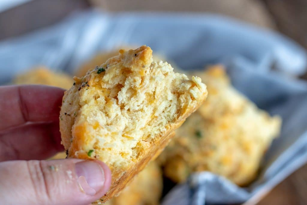 red lobster biscuit in a hand with a bite taken out (inside a biscuit)