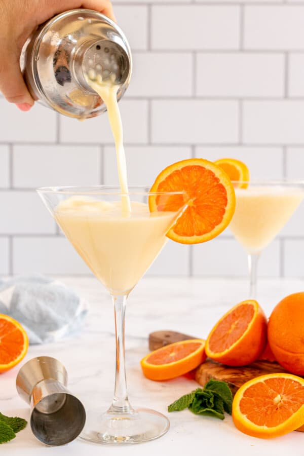 Orange martini being poured into a glass