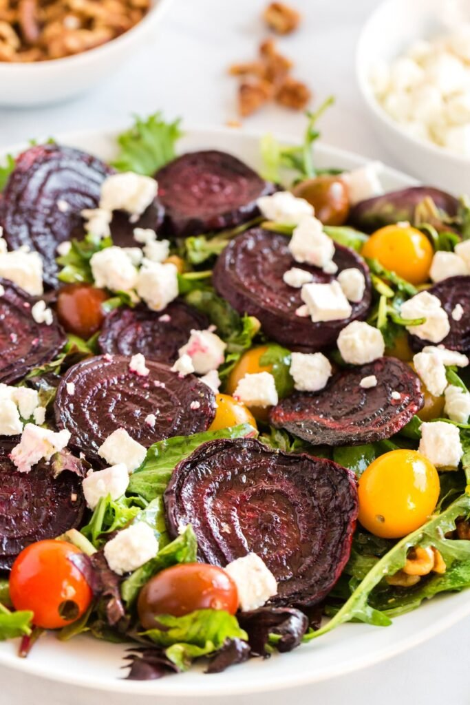 a beet salad close up with red and yellow tomatoes, in a white bowl