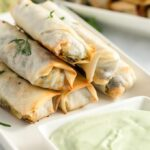 southwestern egg rolls on a white plate with avocado dipping sauce
