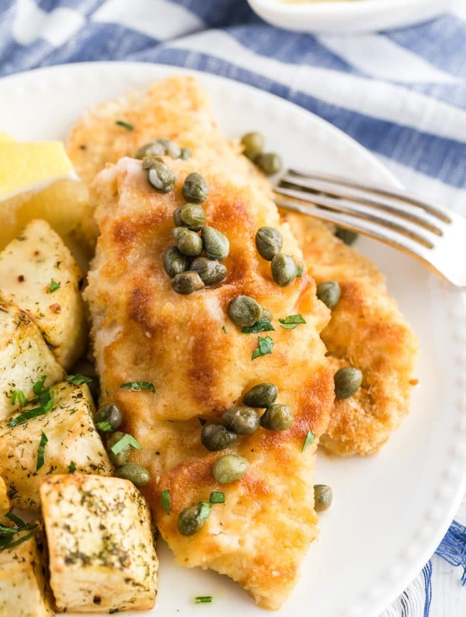 chicken piccata on a plate with capers and a blue and white napkin