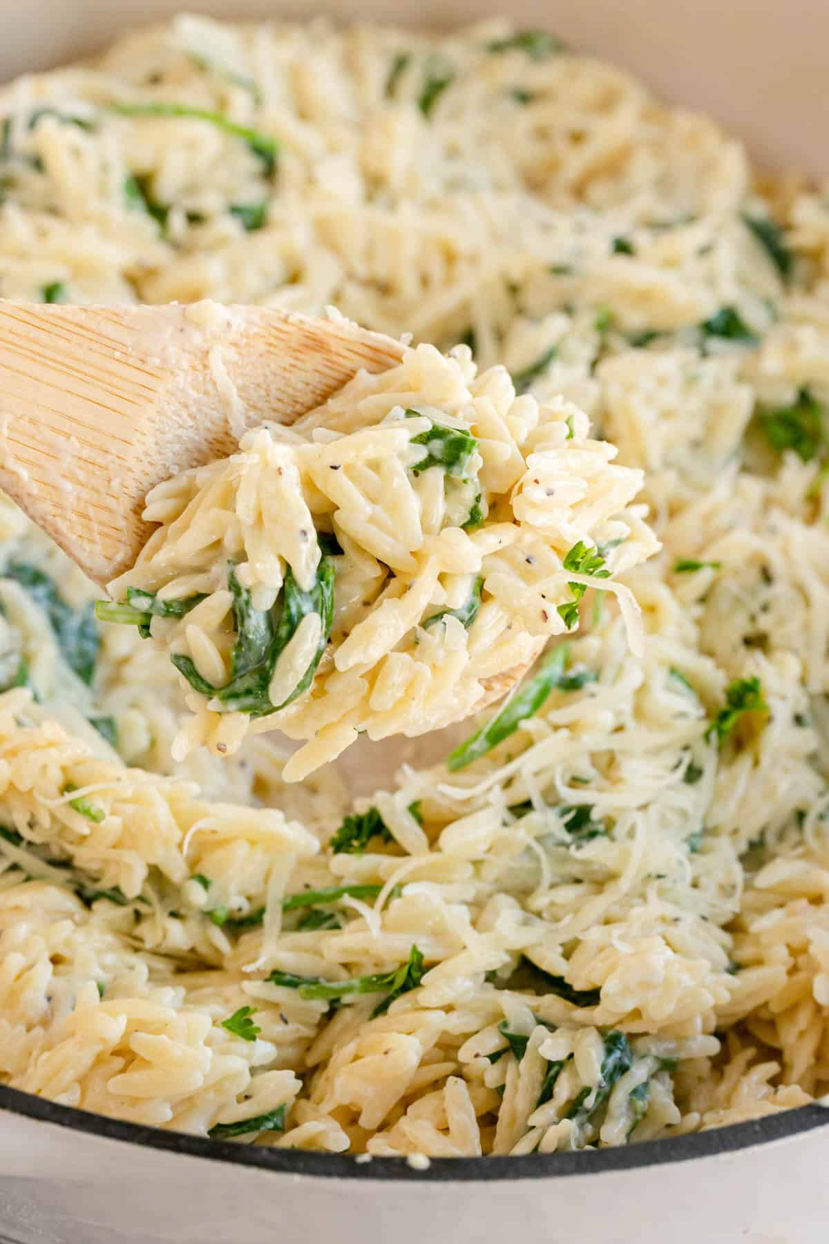 Spinach orzo in a skillet with a wooden spoon