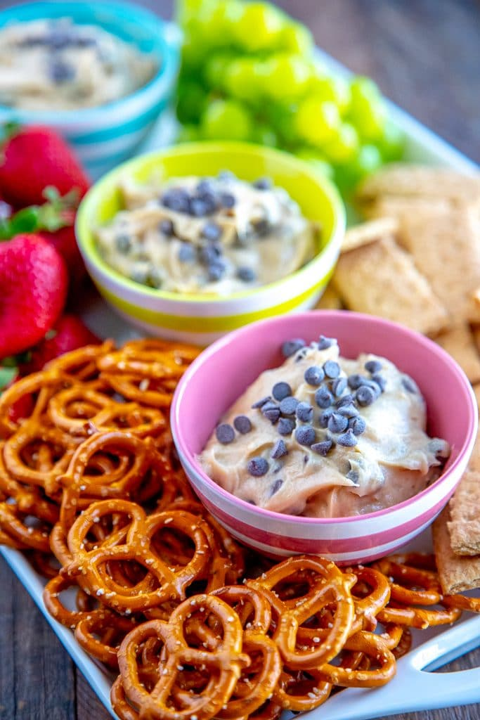 cookie dough dip with pretzels, strawberries, graham crackers and grapes on a white platter