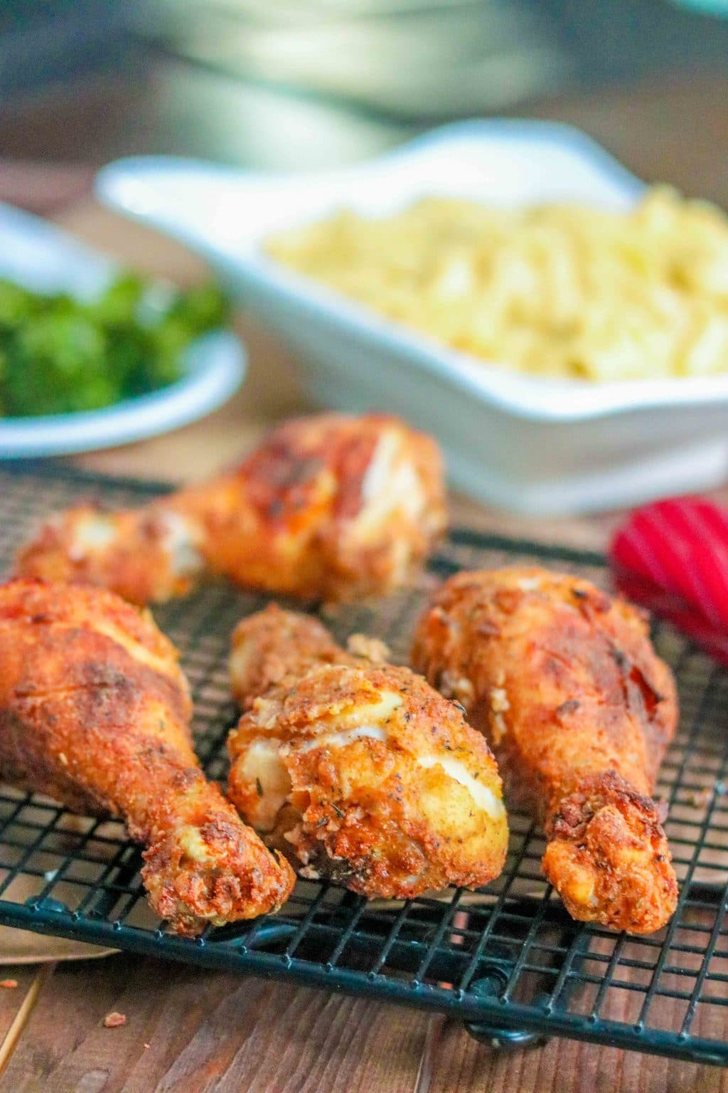 Closeup of oven fried chicken drumsticks on cooling rack with macaroni and cheese in background.