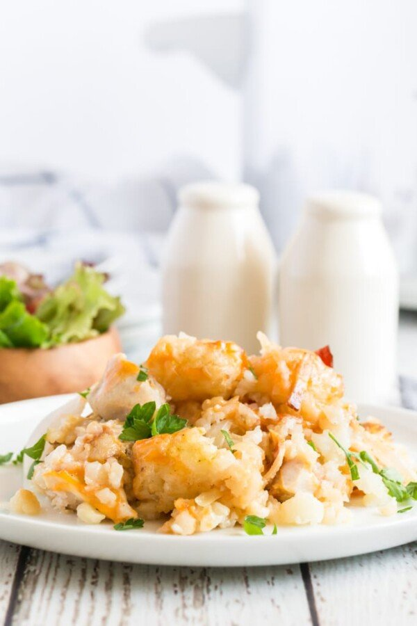 tater tot casserole with salad and white salt and pepper shakers