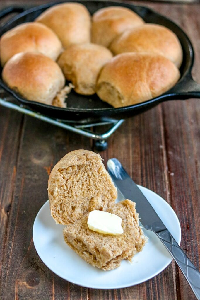Whole Wheat Dinner Rolls split open with butter on a white plate with a knife