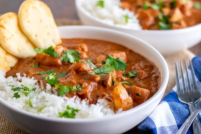 chicken tikka masala in a white bowl with mini naan