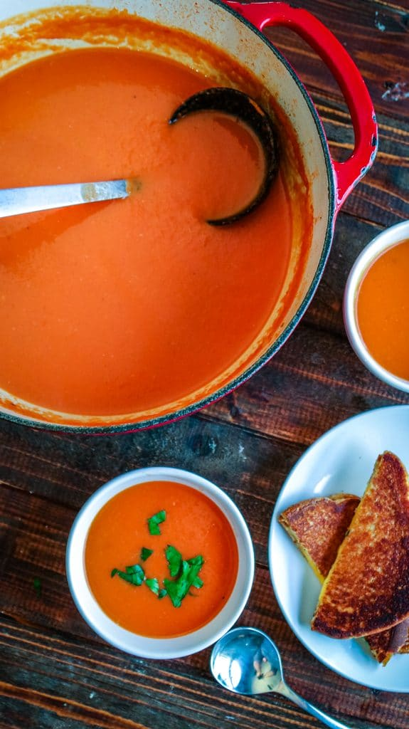 Overhead shot of pot filled tomato soup with white bowl filled with tomato soup on the side.