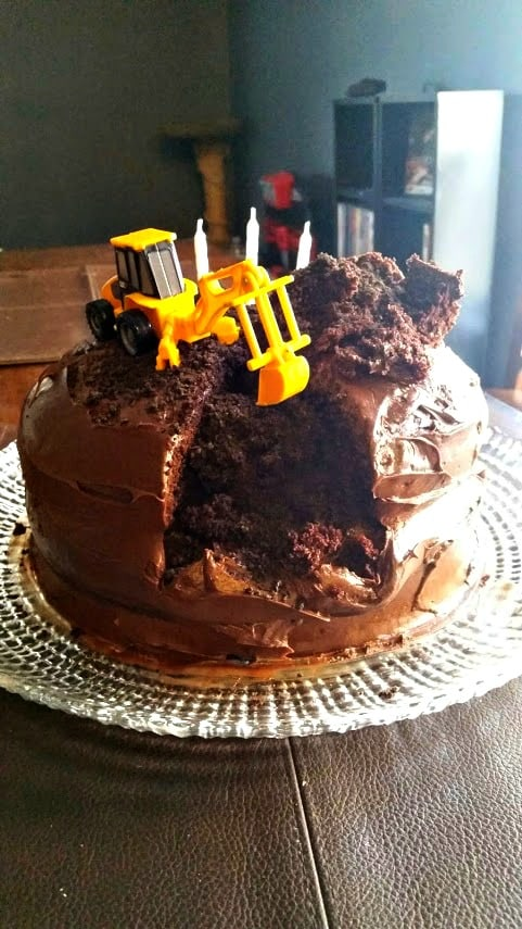 Chocolate cake with big piece scooped out made to look like it was done by toy backhoe on top of cake.