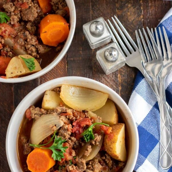 ground beef stew in bowls with a salt and pepper shaker, forks and napkin