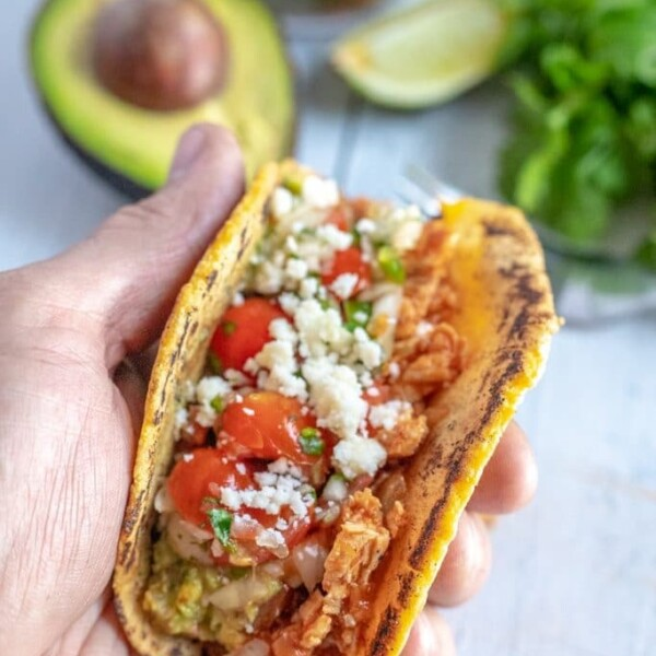 a chicken taco in a hand
