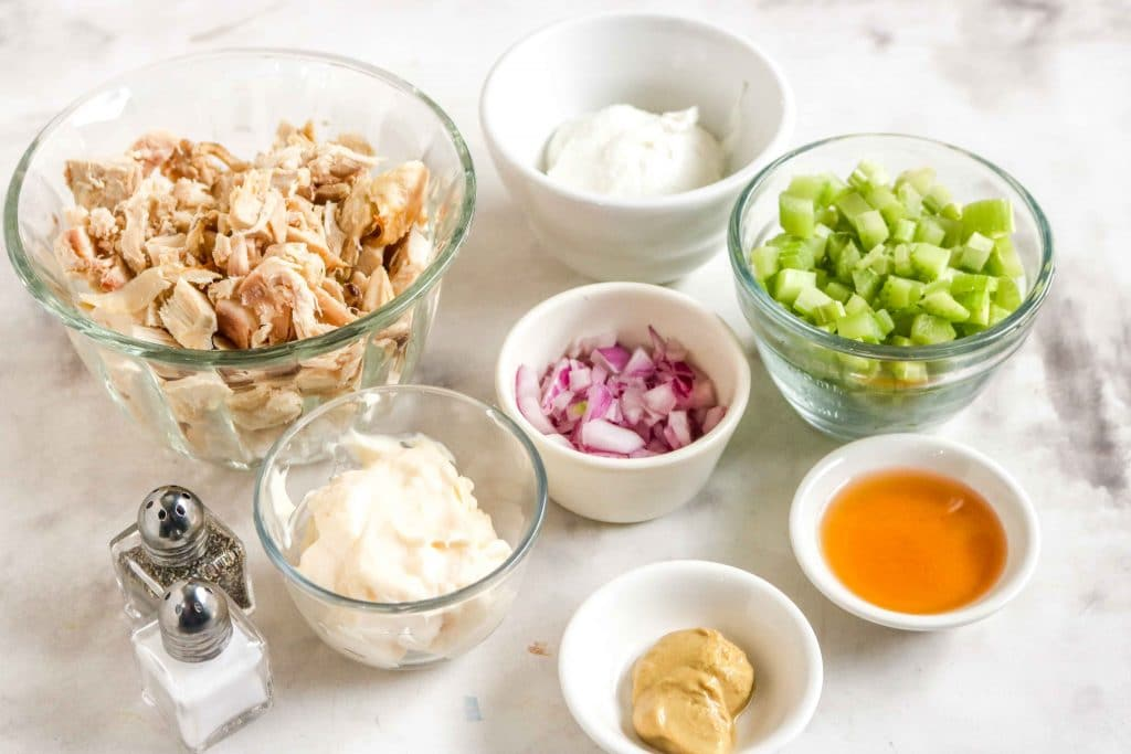Individual chicken salad ingredients divided into bowls on white cloth.