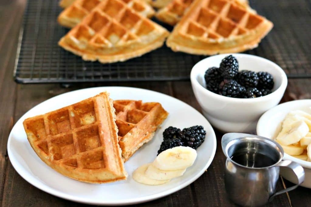 Fresh oatmeal waffles with banana and blackberries on a white plate.