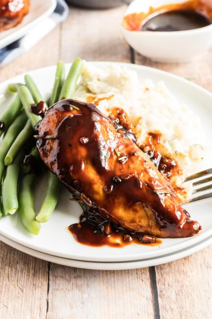 glazed chicken on a plate with green beans