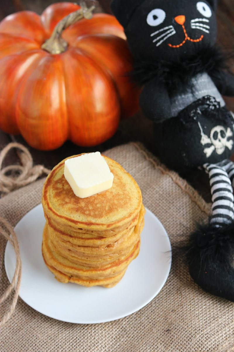 Stack of pumpkin spice pancakes on whit plate sitting on tweed mat next to a pumpkin and a black cat doll.